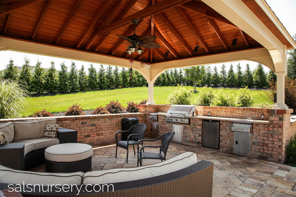 Covered outdoor living area with kitchen and curved couch
