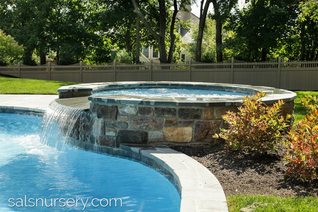 Round stone spa with waterfall into pool