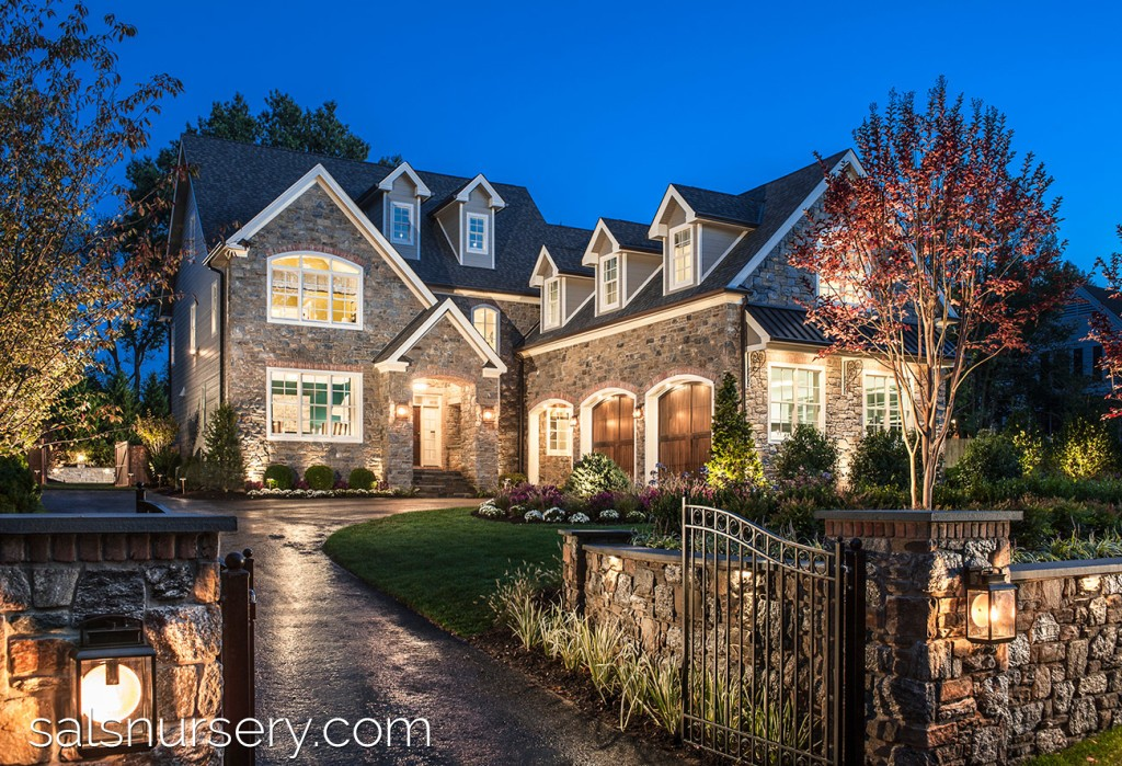 Large house with pristine landscaping and entryway gate